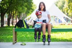 Portait of cute baby boy and his mom wearing inline skates. Sitting on bench in the park Stock Images