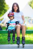 Portait of cute baby boy and his mom wearing inline skates. Sitting on bench in the park Stock Photos