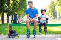 Portait of cute baby boy with inline skating instructor. Portait of cute baby boy with inline skating instructor in the park Royalty Free Stock Photos