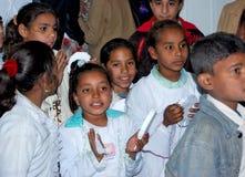 Portait of dark egyptian children smiling gathering at school. In class at school colored cardboard Muslim girl shy, Arab Muslim girl in hejab or veiled in Royalty Free Stock Image