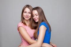 Portait de studio du jeune embrassement jumel de soeurs Photos libres de droits