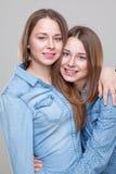 Portait de studio du jeune embrassement jumel de soeurs Photos stock