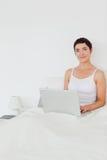 Portait de una mujer dark-haired que usa una computadora portátil Foto de archivo