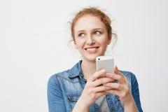 Portait del adolescente blando lindo del pelirrojo con el pelo sucio, mirando a un lado y sonriendo mientras que sostiene smartph Fotografía de archivo libre de regalías