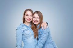 Portait del estudio del abarcamiento gemelo joven de las hermanas Imagenes de archivo