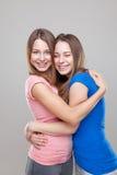Portait del estudio del abarcamiento gemelo joven de las hermanas Foto de archivo libre de regalías