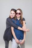 Portait del estudio del abarcamiento gemelo joven de las hermanas Fotografía de archivo