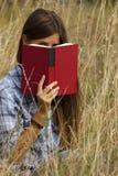 Portait del libro behing nascondentesi della ragazza immagine stock