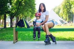 Portait des netten Babys und seiner der Mutter, die Inline-Rochen sitti trägt Stockfotografie