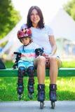 Portait des netten Babys und seiner der Mutter, die Inline-Rochen trägt Stockfotos