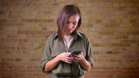 Portait di giovane bella donna dalla testa Brown che guarda smilingly nello smartphone sopra bricken il fondo della parete archivi video