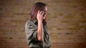 Portait di giovane bella donna dalla testa Brown che parla sul cellulare e che ride sopra bricken il fondo della parete video d archivio