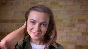 Portait di giovane bella donna dalla testa Brown che tiene i suoi capelli e che posa nella macchina fotografica sopra bricken il  archivi video