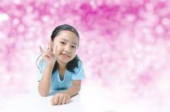 Portait fille asiatique de sourire de la petite montrant le signe de la main d'amour dessus Image stock
