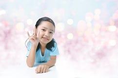 Portait fille asiatique de sourire de la petite montrant le signe de la main d'amour dessus Photo stock