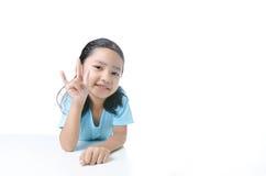 Portait fille asiatique de sourire de la petite montrant le signe de la main d'amour est Image libre de droits