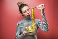 Frustrated beautiful woman with eyeglasses looking at camera while holding bowl with measuring tapes over pink background stock photo
