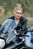 Serious, blonde girl sit on black biker with leather jacket stock photo