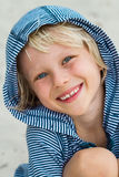 Portait of happy young boy at the beach. Portrait of happy, young boy in striped hoodie at the beach stock photo