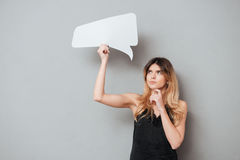 Portait of a lovely pensive girl holding speech bubble. Isolated over grey background royalty free stock images