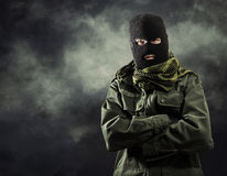 Portait of masked terrorist. Portrait of masked terrorist in military jacket with smoke on background Royalty Free Stock Images