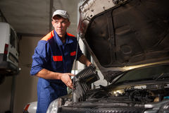 Portait of mechanic fixing car engine in repair shop Royalty Free Stock Photo