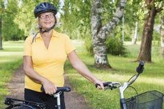 Portait piękna dojrzała kobieta przy parkiem z bicyklem Obrazy Royalty Free