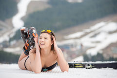 Portait of woman skier is relaxing on the snowy slope in the mountains. Wearing swimsuit, boots and sunglasses Stock Photo