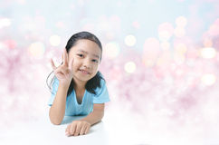 Portait of smile Asian little girl showing  sign of love hand on Stock Photo