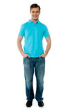 Portait of smiling cool young guy. Standing with arms in his pocket Royalty Free Stock Image