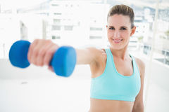 Portait of smiling woman exercising with dumbbell Stock Photo