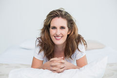 Portait of smiling woman lying on bed Stock Image