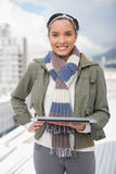 Portait of smiling woman standing outside and holding laptop Stock Images