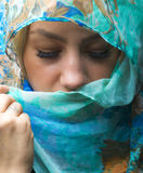 Portait of woman wearing a blue scarf with eyes closed Stock Photography