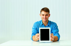 Portait of a young businessman shows the tablet computer screen Royalty Free Stock Image
