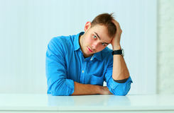 Portait of a young thoughtful businessman sitting at the table Stock Photos