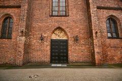 Portal con una escultura y puertas en una iglesia gótica Foto de archivo libre de regalías