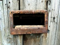 The portal of time. Old gray wooden door with no paint, with old iron, rusty mailbox Royalty Free Stock Images