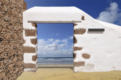 Portal to beach. Old wall standing at the sand beach Stock Photos