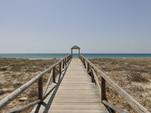 The portal to the beach. Wooden path to reach the beach. has much symbolism as next vacation, or summer beach season road to paradise is hacerca and many more in Stock Photos