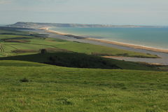 Portand and Chesil Beach. Green fields and a Chapel in the foreground, the Jurassic coast Stock Images