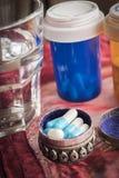 Portapillole metalliche con le pillole bianche e blu Immagine Stock