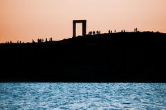 The Portara in Naxos island, Greece. Silhouettes of people gathered to meet the sunset at the Portara on Naxos island, Greece Stock Images