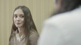 Portarait de jeune belle fille avec de longs cheveux dans la consultation avec le docteur dans l'armoire banque de vidéos