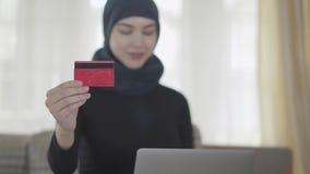 Portarait der jungen schönen moslemischen Frau, die geht, für etwas mit Kreditkarte im Internet-Geschäft unter Verwendung ihres L stock footage