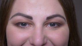 Portarit del primer de la cara femenina caucásica gorda joven con los ojos que miran la cámara con la expresión facial sonriente almacen de video