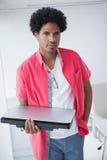 Portarit eines ernsten Geschäftsmannes, der Laptop hält Stockbilder