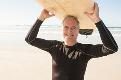 Portarit of smiling senior man carrying surfboard stock photography