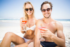 Portarit of young couple in sunglasses having cocktail on the beach Stock Photos