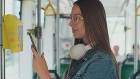 Portarit of a young smiling woman paying conctactless with smartphone for the public transport in the tram. Portarit of a young smiling woman paying stock footage
